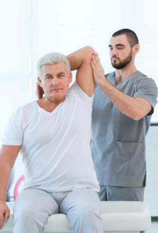 therapist assisting the senior man