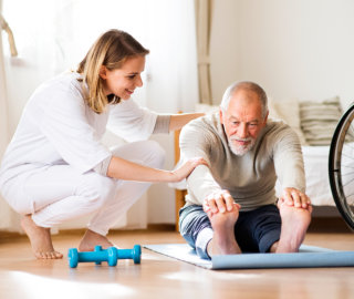 A nurse or a physiotherapist helping a senior man exercise