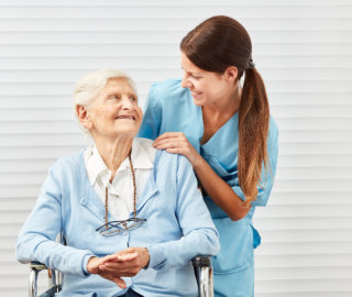 Smiling senior citizen in wheelchair and nurse